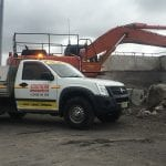 White southern autoglass van and and a client's excavator in the background at a construction site