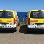 2 yellow southern autoglass service vans parked near the sea